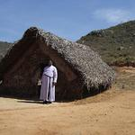 Rev. G. Rajadurai standing in front of a shed that has been put up for worship on a newly purchased site, where mass baptisms had taken place last year.